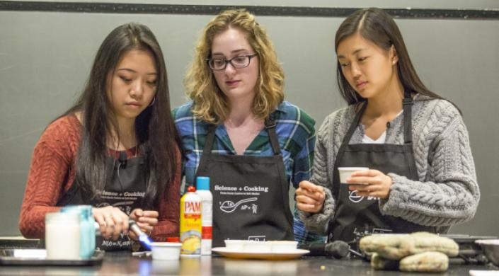 image of students using a soufflé torch to give a golden brown color to chocolate chip cookies baked in the microwave
