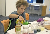 image of Miles Higgins, 12, a Boston resident and seventh-grader Clarence R. Edwards Middle School, adds lemon juice to a red cabbage juice solution during a -Science and Cooking for Kids- lab session